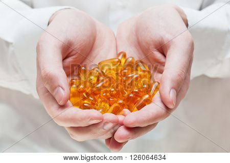 Doctor's hand with gel capsules. Omega-3 fish oil