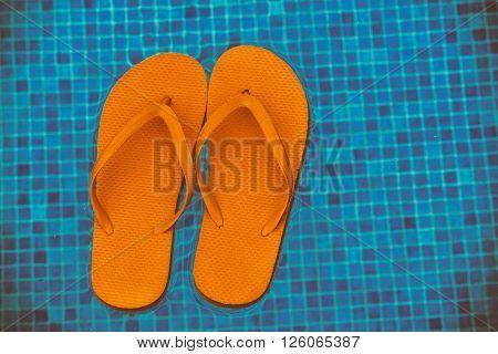 orange flip flops floating in  blue pool water, retro toned