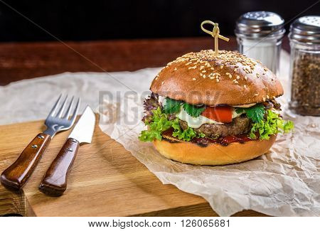 Burger on the wooden table with with knife and fork. burger with beef