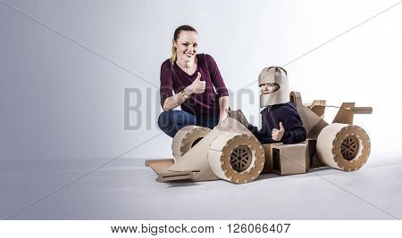 Mother and son playing with a large cardboard racing car. thumbs up. happy family.