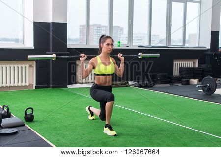 athletic woman doing lunges with barbell, working out legs and glute muscles.