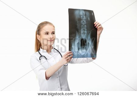 Woman doctor in a robe looking at the light picture of human pelvis . An isolated on white background