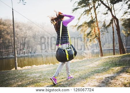 Young beautiful sporty woman walking from the camera in a park with bag