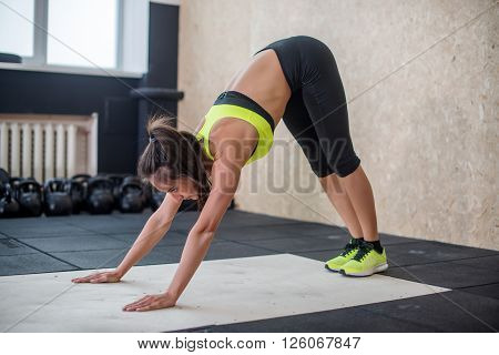 fit woman performing downward dog pose, doing yoga in gym.