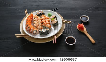 Japanese food restaurant, sushi maki gunkan roll plate or platter set. Set with colorful chopsticks, ginger, soy, wasabi. Sushi at black rustic wood background and black stone.