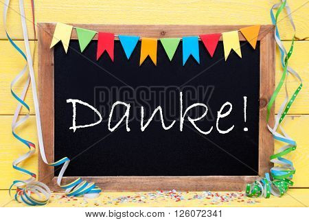 Chalkboard With German Text Danke Means Thank You. Party Decoration Like Streamer, Confetti And Bunting Flags. Yellow Wooden Background With Vintage, Retro Or Rustic Syle