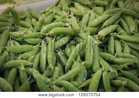 A pile of sugar snap peas for sale in a vendor's stall at a farmer's market.