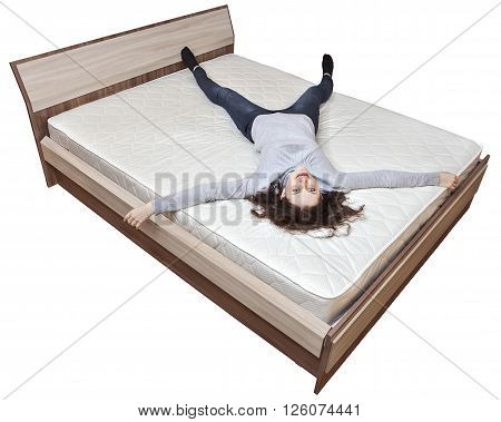 One young Caucasian woman relaxing on a spring mattress huge wooden bed isolated on white background.