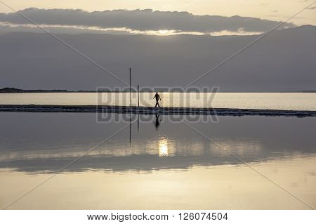 Man wearing black sports clothes walking on headland at the Dead Sea in early morning under rising sun with mountains background