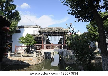 An asian style bridge and architecture over the canals within the water town of Luzhi located in Jiangsu province China.
