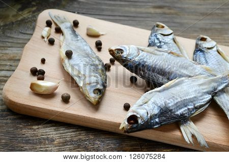 Salty stockfish cod on wooden board with garlic and pepper