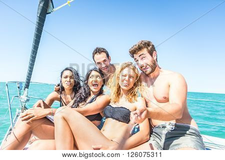 Group of friends taking selfie from the boat - Multi-ethnic young people having fun and partying on a sailing ship