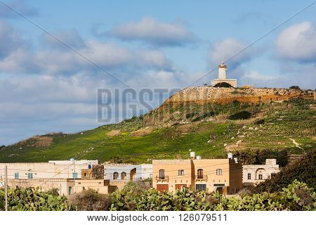 Panorama view on fields and lighthouse on the top of mountain. Gozo island Malta.