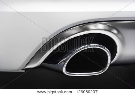chrome exhaust pipe of powerful sport car with white bodywork and grey shiny aluminum detail