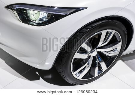 Car headlight and wheel with silver disk of comfortable sport sedan with white bodywork, luxury class vehicle