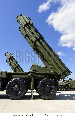 Heavy missile launchers on powerful mobile transportations standing in row ready to attack, modern military industry, antiaircraft forces, blue sky and white clouds on background