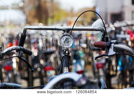 handlebar of a bicycle standing between others at a bicycle parking lot