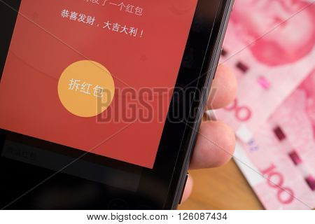 ZhongshanChina-Feb 212016:getting a mobile red pocket on WeChat for Chinese new year with RMB on background.FEB 8 is the 1st day of Year of Monkey & sending receiving red pockets online is very popular in China.