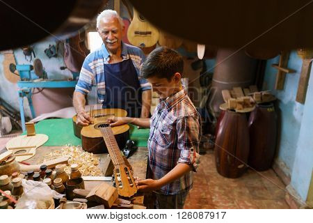 Small family business and traditions: old grandpa with grandson in lute maker shop. The senior artisan teaches how to tune a classic guitar to the boy holding a diapason.