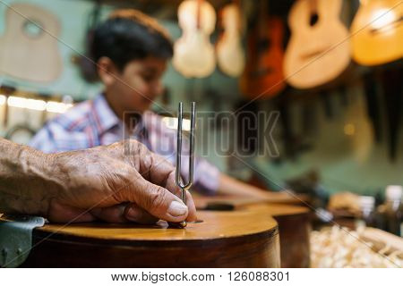 Small family business and traditions: old grandpa with grandson in lute maker shop. The senior artisan teaches how to tune a classic guitar to the boy. Closeup of hand holding a diapason on guitar body.