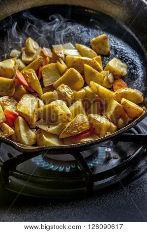 Potatoes, onions, and carrots frying in a cast iron skillet over a flame.