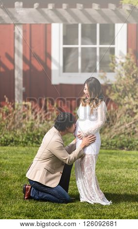 Husband kissing abdomen of expecting mom while kneeling in front of her on grass. Haze light effect applied to image.