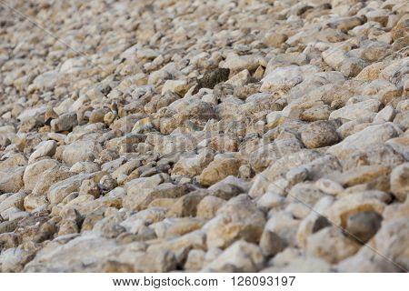 White yellow brown big and small natural stones levee at Dead Sea background