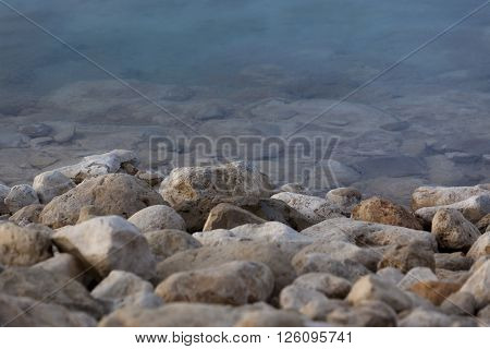 White yellow grey natural boulders with salt levee on blue water edge of Dead Sea