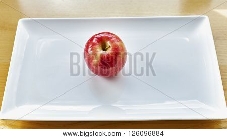 Red Apple on white rectangular glossy plate