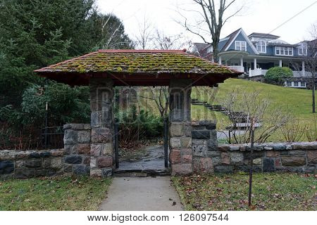 A stone gateway stands in front of a large lakefront mansion on a hilltop along Glenn Drive in Harbor Springs, Michigan.