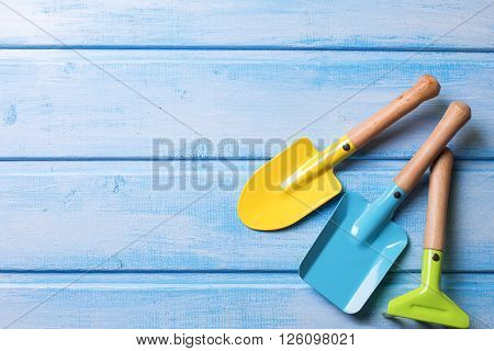 Garden tools or tools for playing in sand for kids on blue painted wooden planks. Place for text.