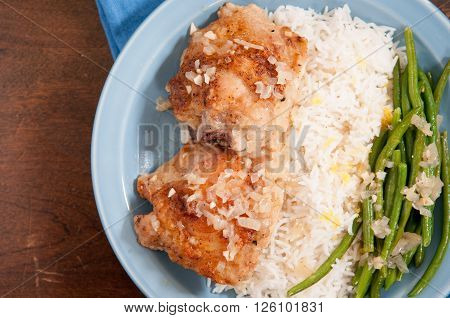 cripsy fried chicken thighs with vegetables over rice in a lemon sauce