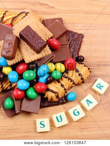 Heap of candies and cookies with word sugar on wooden table too many sweets concept of unhealthy food