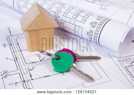 House shape made of wooden blocks rolls of diagrams and home keys lying on electrical construction drawings of house concept of building house