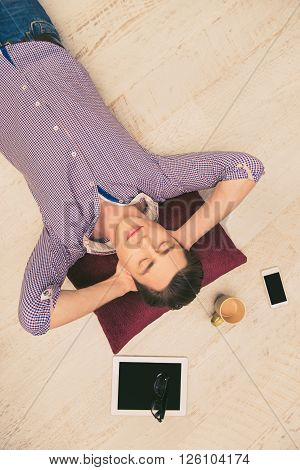 Top View Of Handsome Young Man Lying On Floor With Closed Eyes