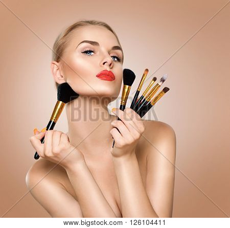 Beauty Woman with Makeup Brushes. Natural Make-up for Blonde Model Girl with Blue Eyes. Beautiful Face. Perfect Skin. Applying Holiday Makeup, orange color lipstick and manicure over beige background