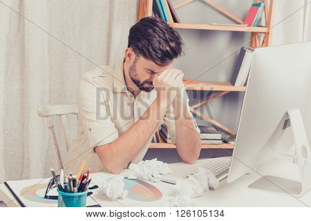 Portrait Of Tired Depressed Young Man Sitting At The Table