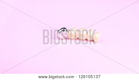 image of one dental prosthesis on pink background