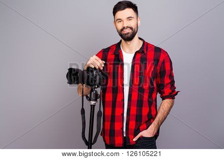 Portrait Of Handsome Young Cameraman Standing In Studio With Camera
