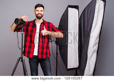 Handsome Photographer With Camera In Photo Studio Gesturing