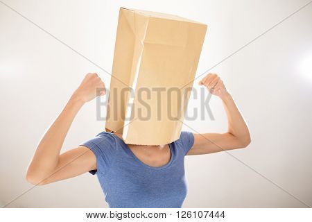 Woman with bag covering her head and showing her biceps