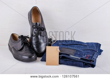 Set of men's clothing shoes jeans and a belt with blank tag on white wooden background