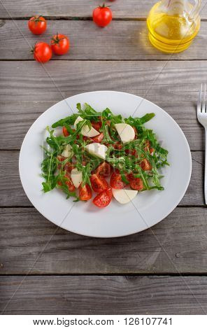 salad of arugula tomato and mozzarella in a white plate on a wooden table top view. Tasty and healthy food