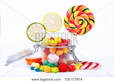 bright multicolored lollipops candy and chewing gum in the jar of glass on a white background