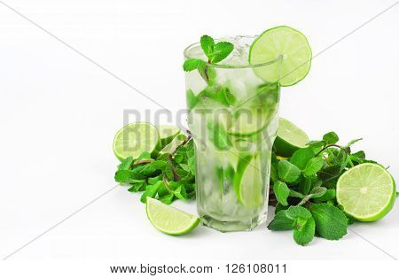 mojito cocktail with lime and mint in tumbler glass in mint leaves on white background with copy space
