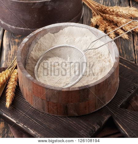 Flour in a wooden bowl with sieve on vintage board on a dark old table closeup. Square frame