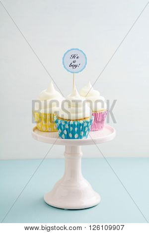 Three baby shower cupcakes for a boy with buttercream frosting on a cake stand