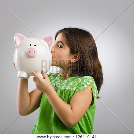 Beautiful and happy young girl holding a piggybank