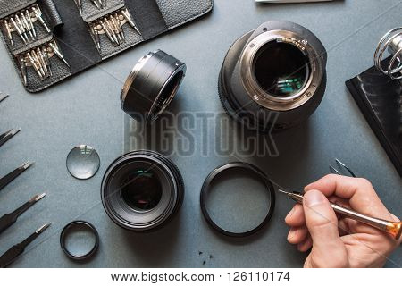 Precision optical dslr lens service, adjustment and alignment. Camera lens repair set in photo engineer workplace. Maintenance support of photographic 50 1.4 photo camera lens.