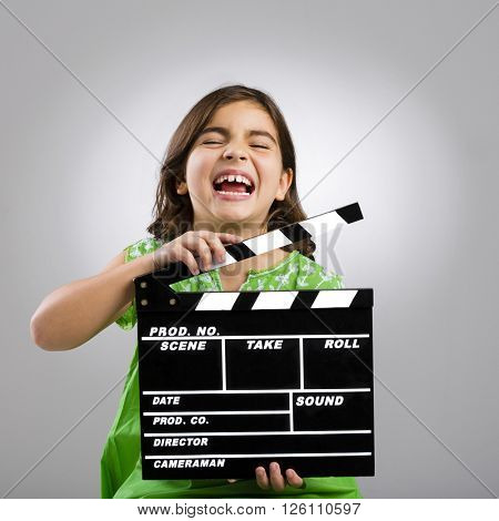 Studio portrait of a little girl playing as a young film director